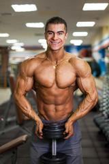 bodybuinder with dumbbellin gym