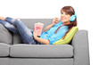 Girl listening music and eating popcorn on sofa