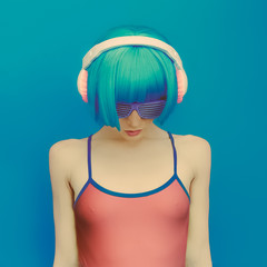 unreal DJ girl in fashionable headphones listening to music