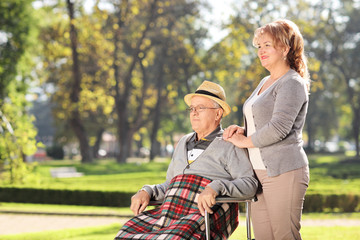 Man in wheelchair sitting with his wife in park