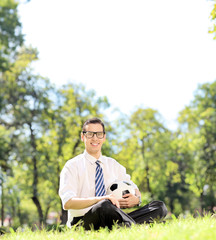 Young guy holding a football in park seated on the grass