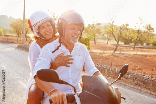 Mature Couple Riding Motor Scooter Along Country Road - 72632057