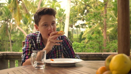 Young teenager eating toast and drinking water on terrace