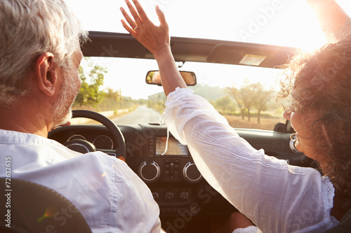 Leinwandbild Motiv Mature Couple Driving Along Country Road In Open Top Car