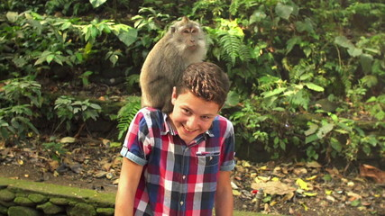 Happy young teenager feeding monkey in Ubud Monkey Forest in Bal