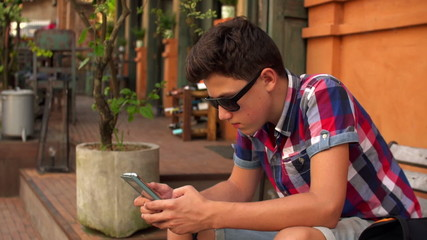 Young teenager sending sms, texting on smartphone while sitting