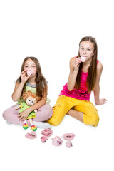 Two little girls play drinking tea