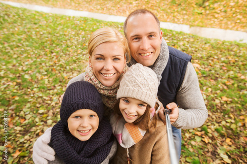 canvas print picture happy family with selfie stick in autumn park