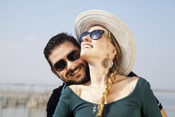 Hombre con barba abrazando a mujer con gafas de sol y sombrero
