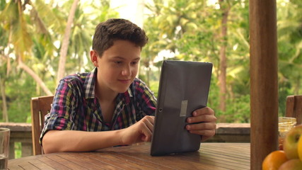 Young teenager using tablet computer on terrace