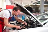 Fototapety Automechaniker in einer Werkstatt repariert Fahrzeug