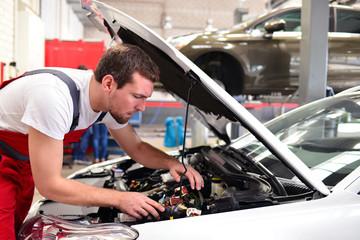 Automechaniker in einer Werkstatt repariert Fahrzeug