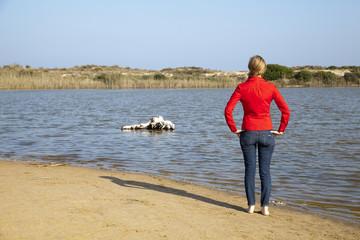 Mujer de rojo sobre la arena observando lago