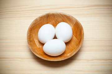 Three white chicken eggs in a plate