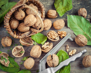 Walnuts, nutcracker and basket on old table, top view.