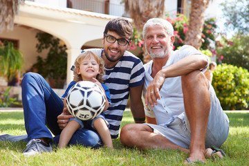 Grandfather Sitting In Garden With Son And Grandson