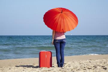 Turista con maleta y sombrilla rojas mirando el mar