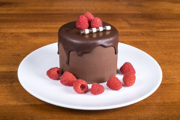 Rich Chocolate Cake Decorated with Raspberries On White Plate
