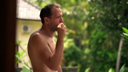 Attractive man brushing teeth in towel standing on terrace