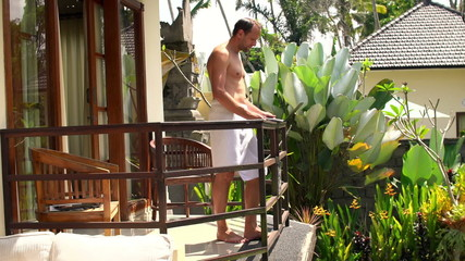 Handsome man using laptop in towel standing on terrace