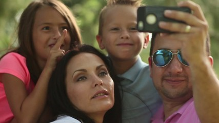 video of a family taking selfies with smartphone in park