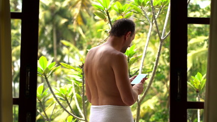 Handsome man in towel talking photo with cellphone on terrace