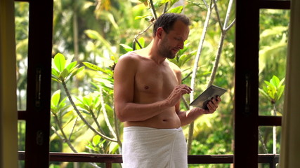 Young man in towel using tablet computer standing on terrace