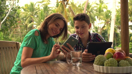Mather and her son using smartphone and talking on terrace