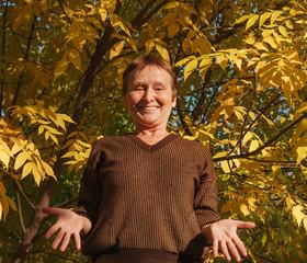 Elder woman shrug shoulder on the background of colorful leaf