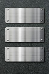 three stainless steel metal plates on black background