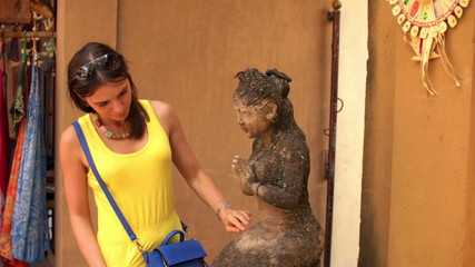 Pretty woman looking and checking ancient sculpture