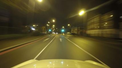Time lapse of a car driving along a road at night and parking