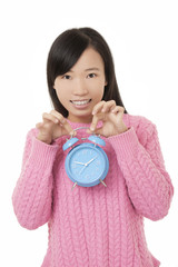Beautiful Chinese woman holding a blue alarm clock