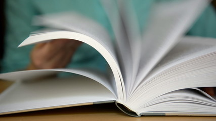 Hands turn pages of the book