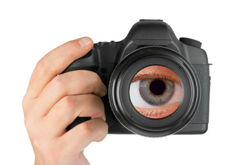 Photo camera in hand and eye in lens