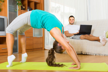 Couple doing yoga with laptop