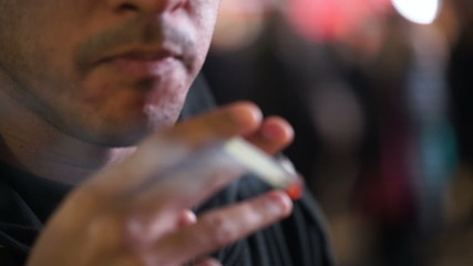 Close up of a man lighting up a cigarette to smoke