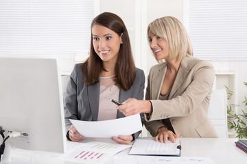 Erfolgreiche lachende Frauen schauen in den Computer im Büro