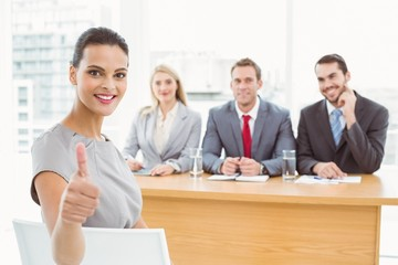 Woman gesturing thumbs up in front of corporate personnel office