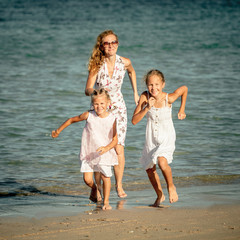 Happy family running at the beach at the day time