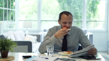 Businessman eating breakfast and reading newspaper in the mornin