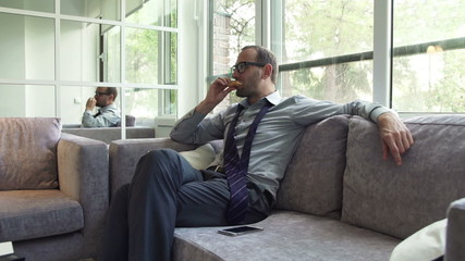 Businessman eating sandwich and relaxing on sofa by the window a