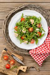 Salad with arugula, tomatoes cherry, mozzarella, pine nuts and b