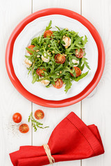 Salad with arugula, tomatoes cherry and mozzarella on white and