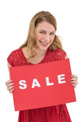 Smiling blonde showing a red sale poster