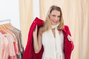 Smiling young blonde woman trying a jacket
