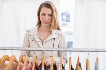 Pretty blonde looking at camera by clothes rail