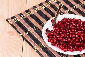 Pomegranate seeds on plate.