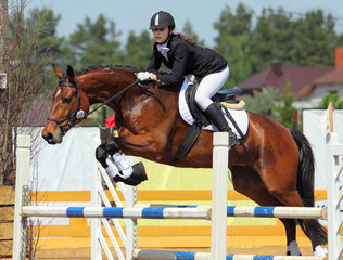 Young girl on the horse at jumping competition