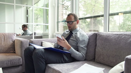 Businessman comparing data on smartphone and documents sitting o